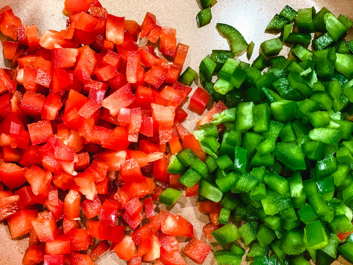 Green and Red peppers diced on a cutting board.