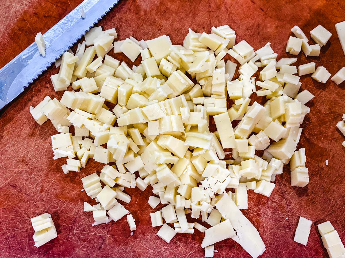 Cheese sliced into small pieces on a cutting board.