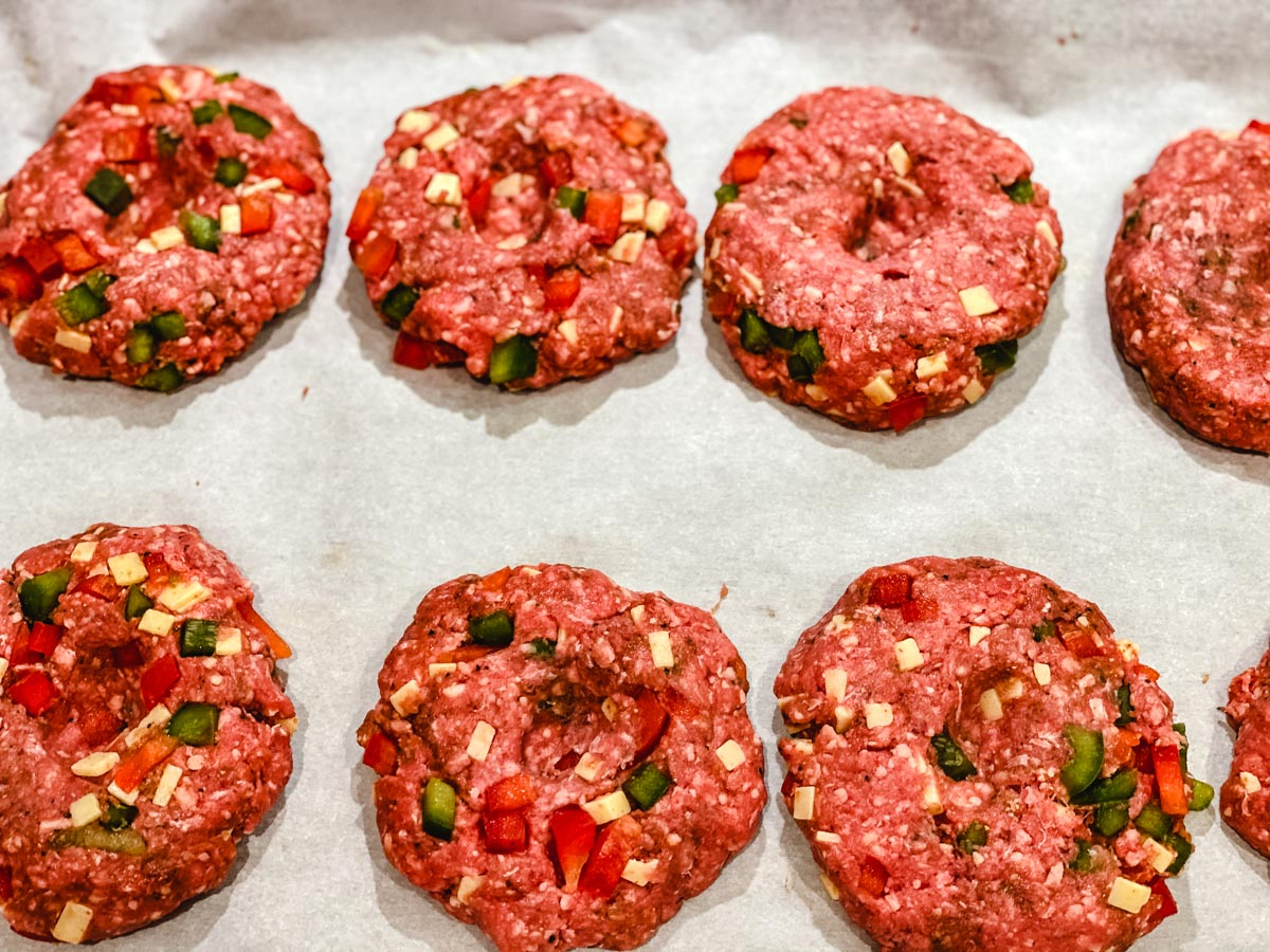 Raw burgers on a piece of parchment paper.