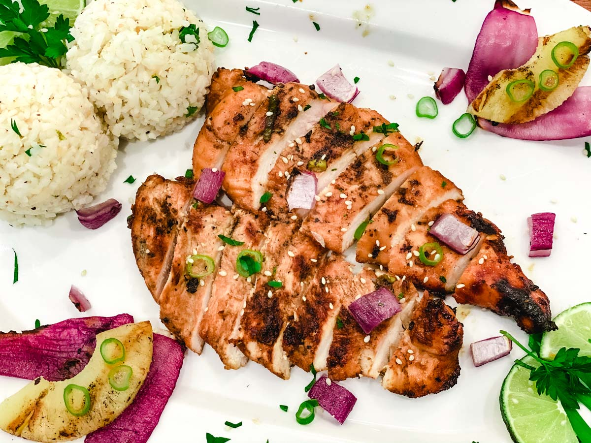 Sliced chicken with rice, pineapple, red onions and lime on a white plate.