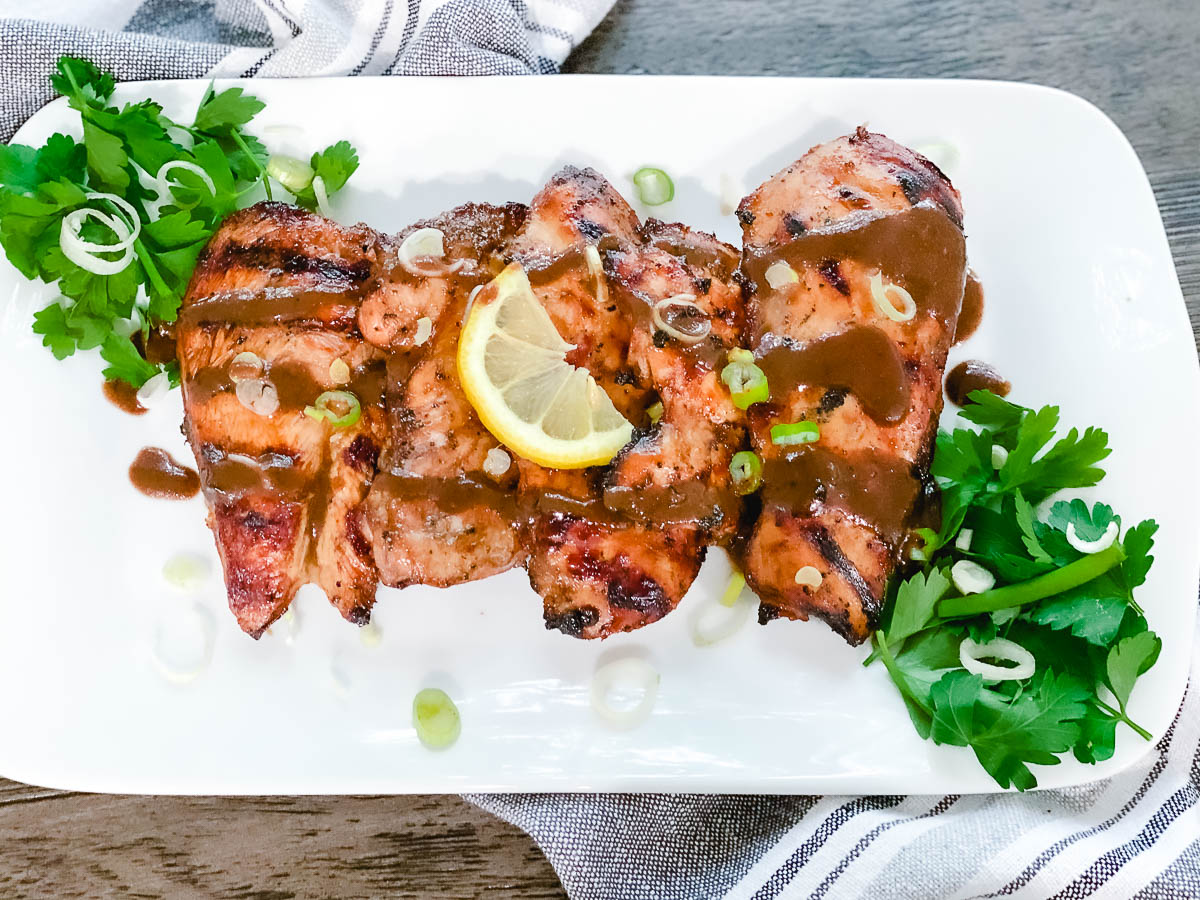 Balsamic Lemon Marinade Chicken on a white place with lemons and parsley.