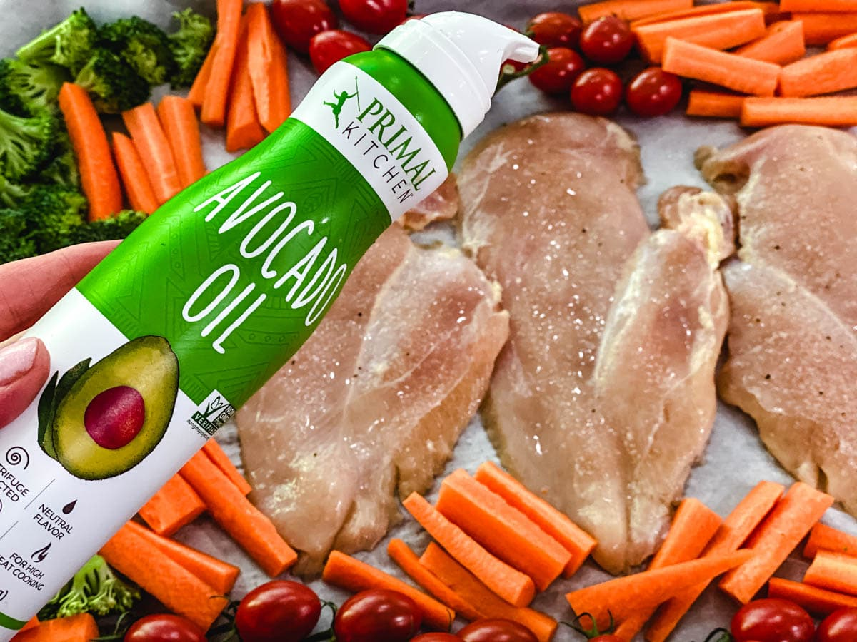 Raw chicken on a baking sheet surrounded by carrots, broccoli, and tomatoes with a spray can of oil.