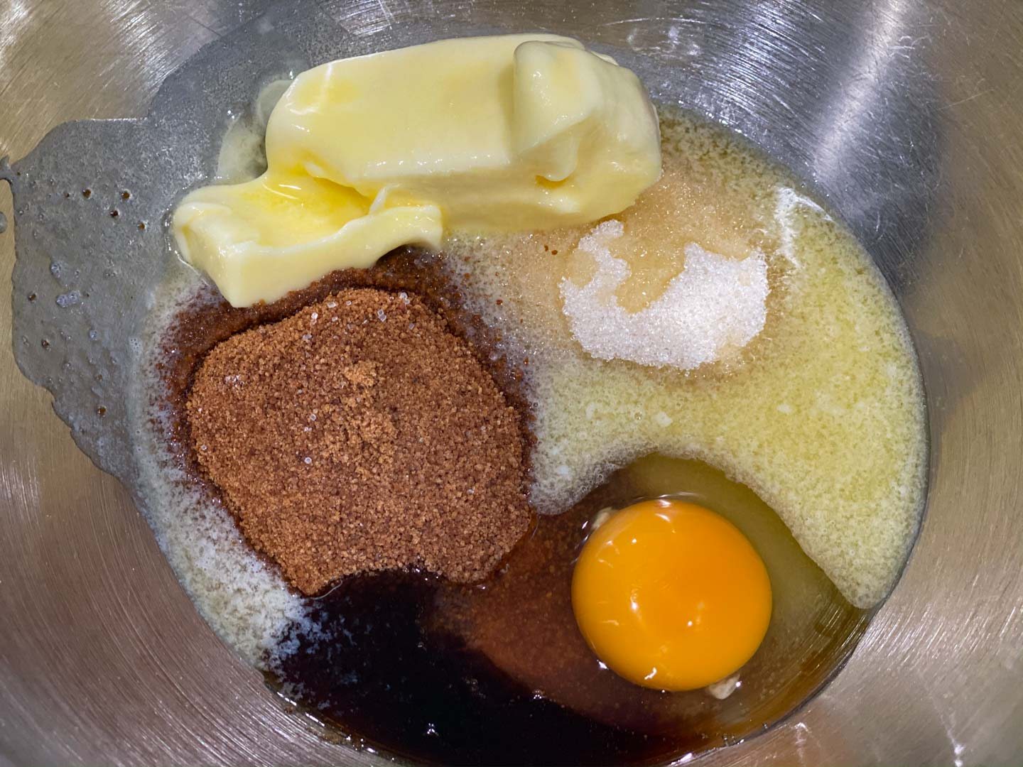 Sugar, Coconut sugar, egg, butter, and vanilla in a mixing bowl.