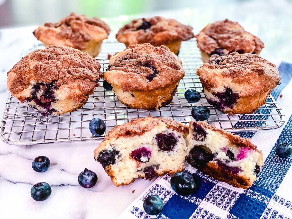 Gluten free blueberry muffins on a cooling rack with fresh blueberries.
