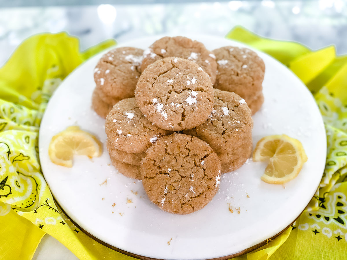 Gluten free lemon cookies on a plate with a yellow napkin.
