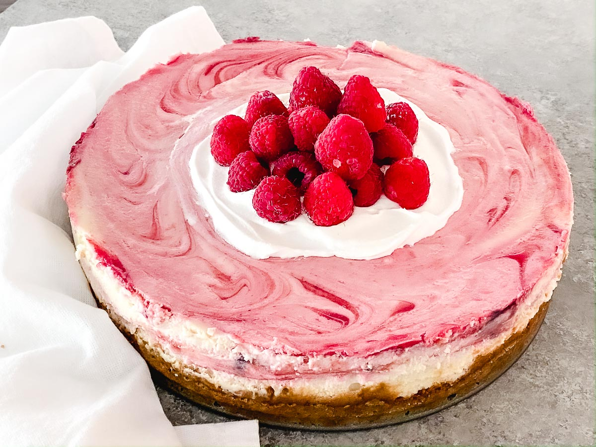 Gluten free raspberry cheesecake with whipped cream and berries on top.