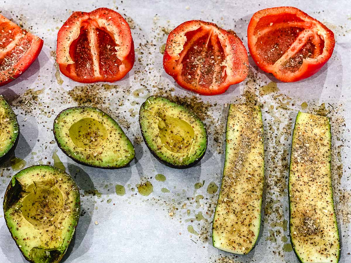 Red peppers, zucchini, and avocados on a piece of parchment paper before they are grilled.