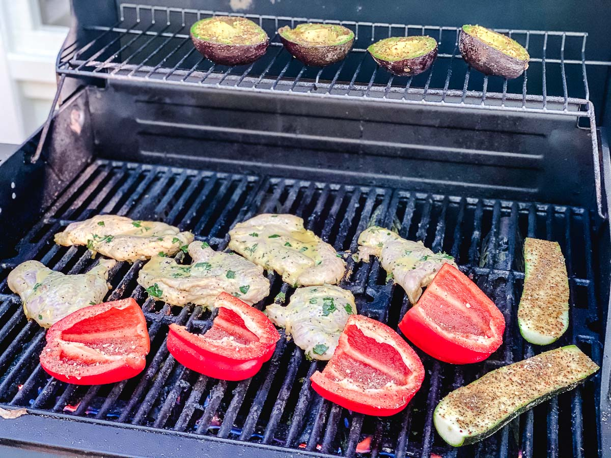 Red Peppers, chicken, zucchini, and avocados on a grill.
