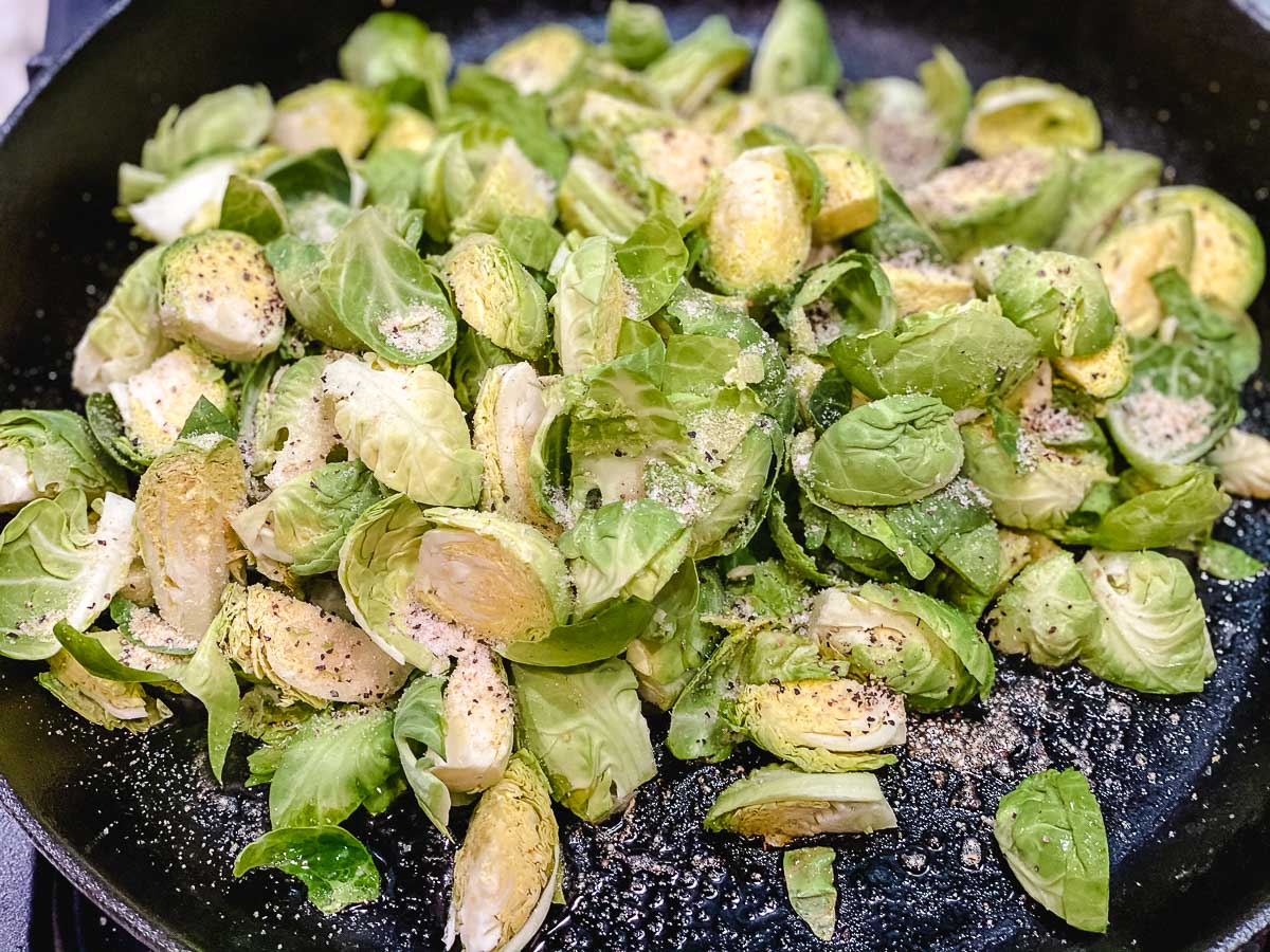 Brussel sprouts in a cast iron skillet with salt, pepper, onion and garlic powder.