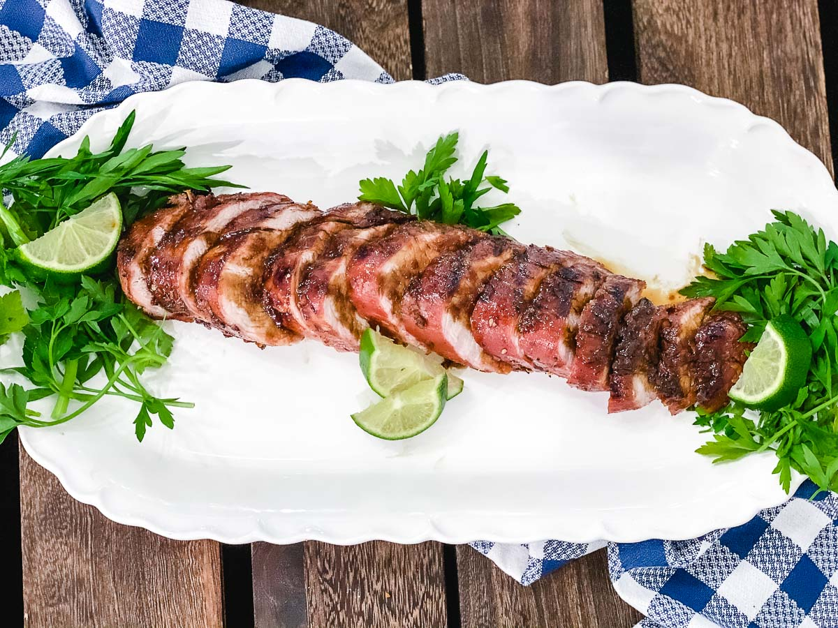 Grilled sweet bbq Thai pork tenderloin on a white plate with parsley and limes for garnish.