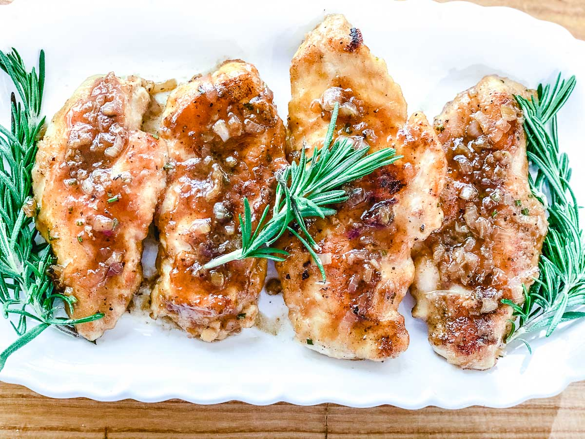 Sweet Shallot Chicken on a white plate with fresh rosemary.
