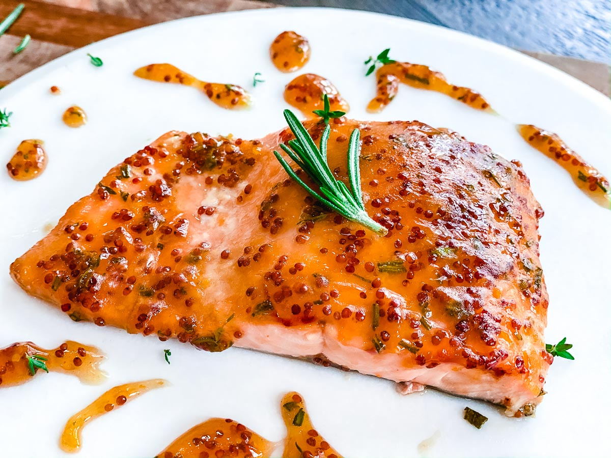 Salmon with apricot mustard glaze on a white plate.