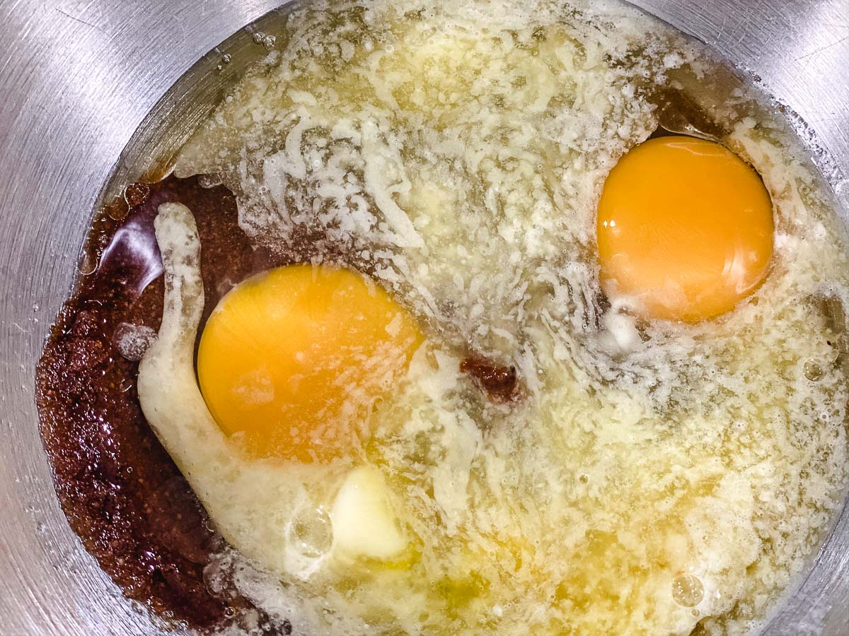 Eggs, butter, coconut sugar, sugar, and oil in a bowl.