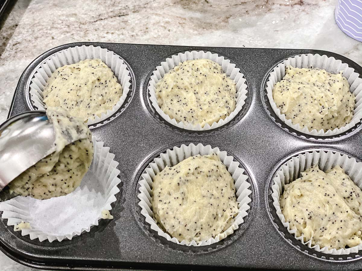 Gluten Free Lemon Poppy Seed Muffin batter in paper lined cups in a muffin tin.