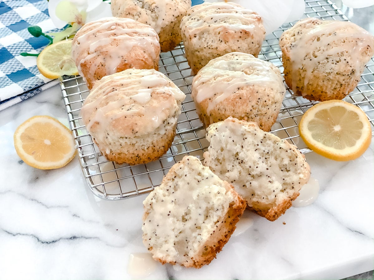 Gluten Free Lemon Poppy Seed Muffins on a wire rack with a lemon glaze drizzled down on top.