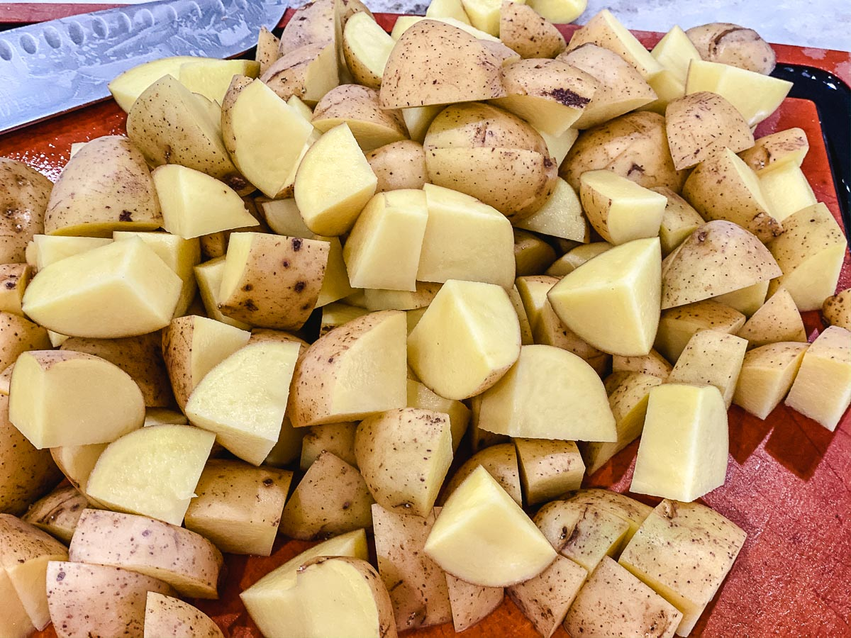 Yukon Gold potatoes cut into cubes on a cutting board.