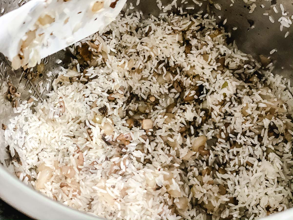 Rice being stirred in an Instant Pot with mushrooms and onions.