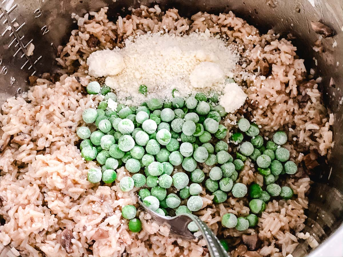 Instant Pot Risotto with frozen peas and fresh parmesan being stirred in.