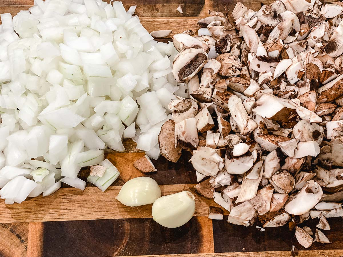 Sliced onions, mushrooms and 2 garlic cloves sitting on a cutting board.