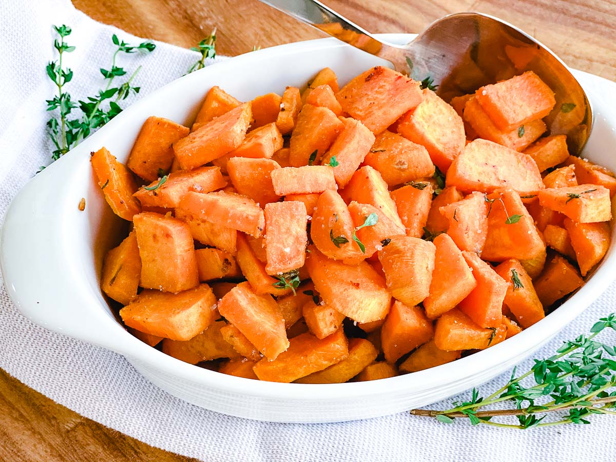 Maple Dijon Sweet Potatoes in white bowl with thyme and rosemary.