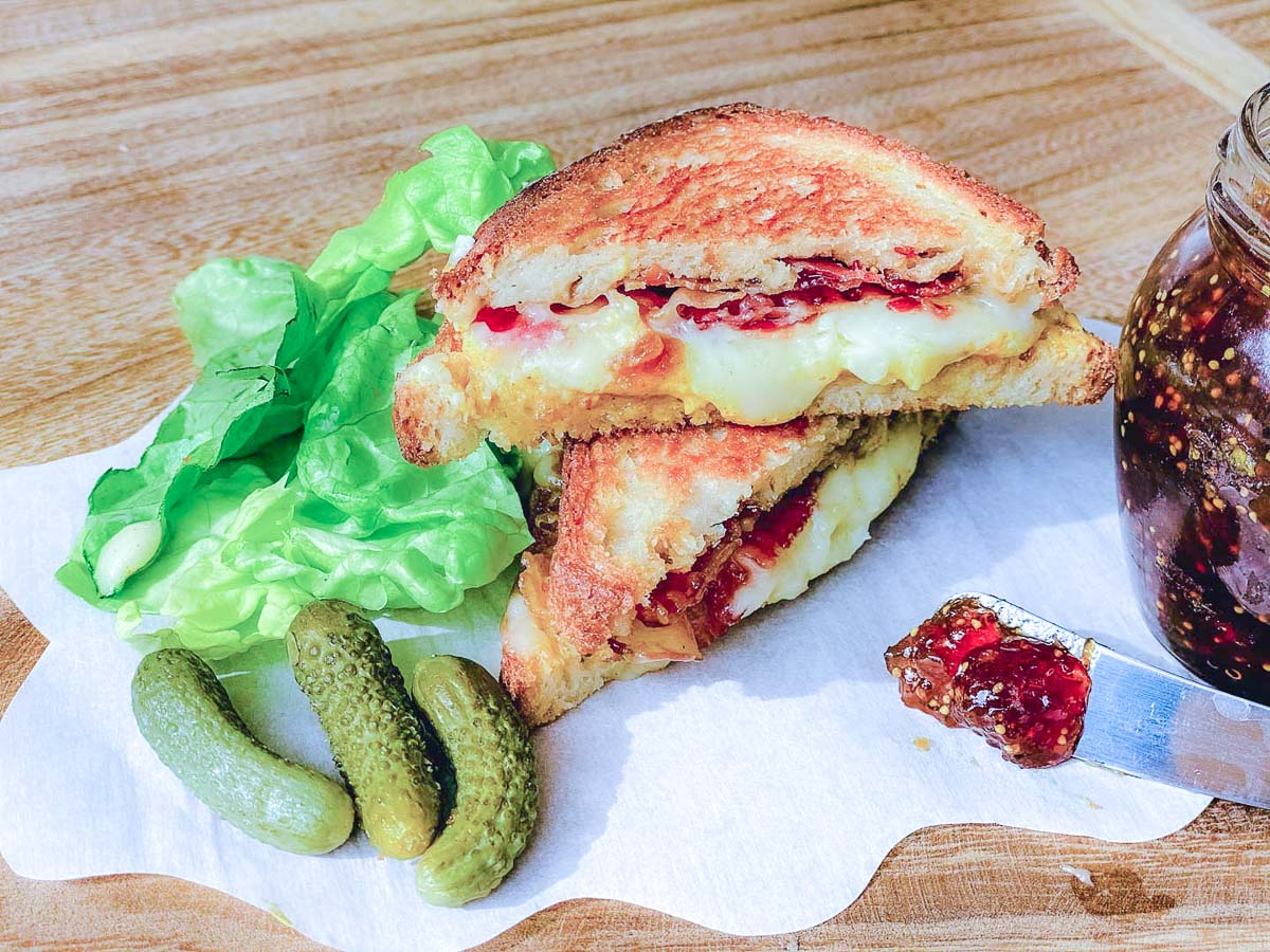Gluten free grilled cheese sandwich with pickles, lettuce and fig jam off to the side.