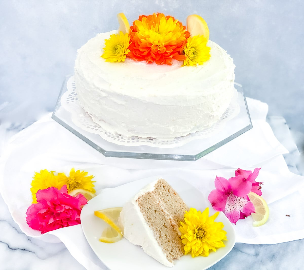 Gluten free lemon cake on a glass plate with flowers and fresh slices of lemon.