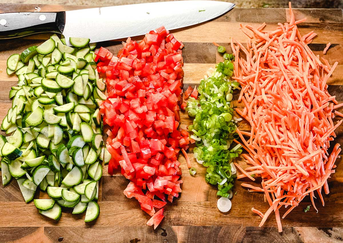 Sliced zucchini, red peppers, spring onion and carrots on a cutting board.