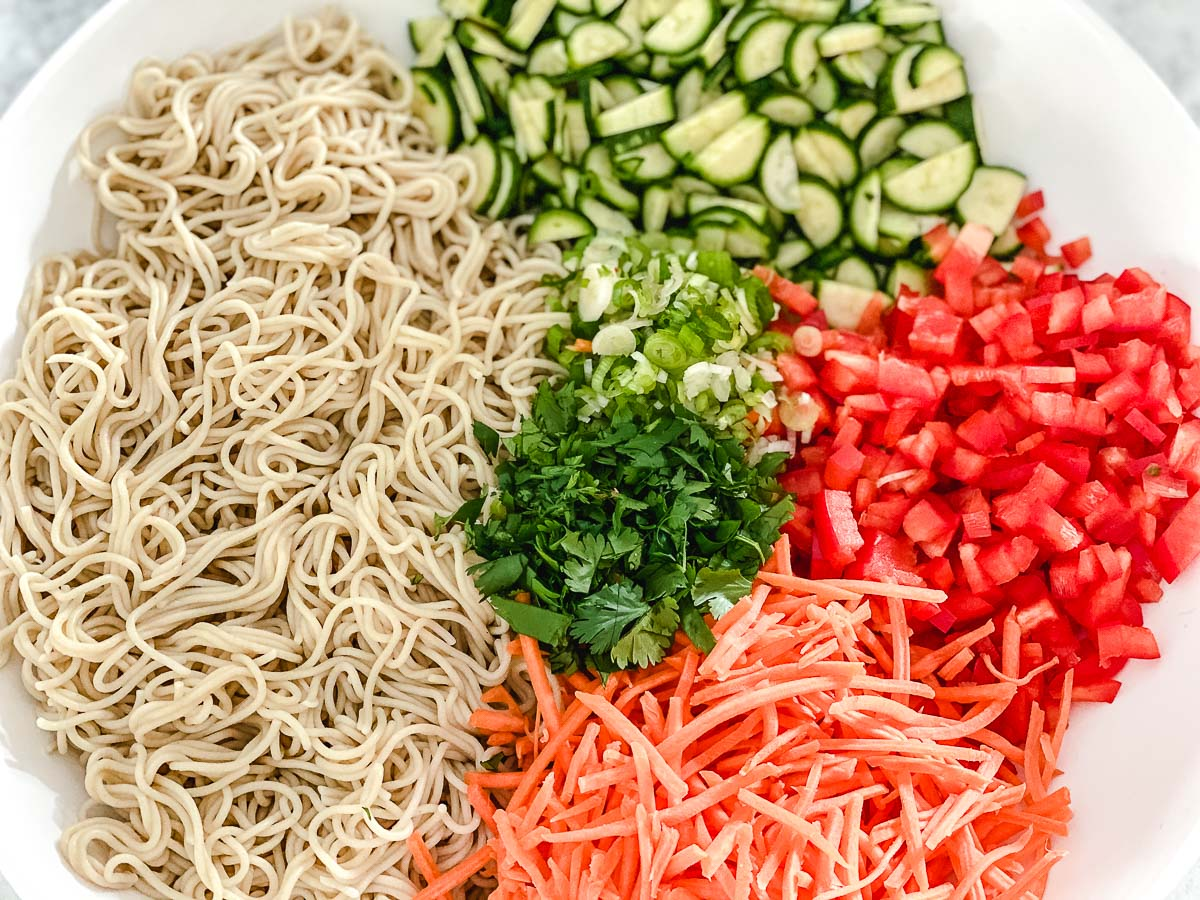 Cooked noodles, sliced zucchini, red peppers, carrots spring onions, and shredded carrots in a white bowl.
