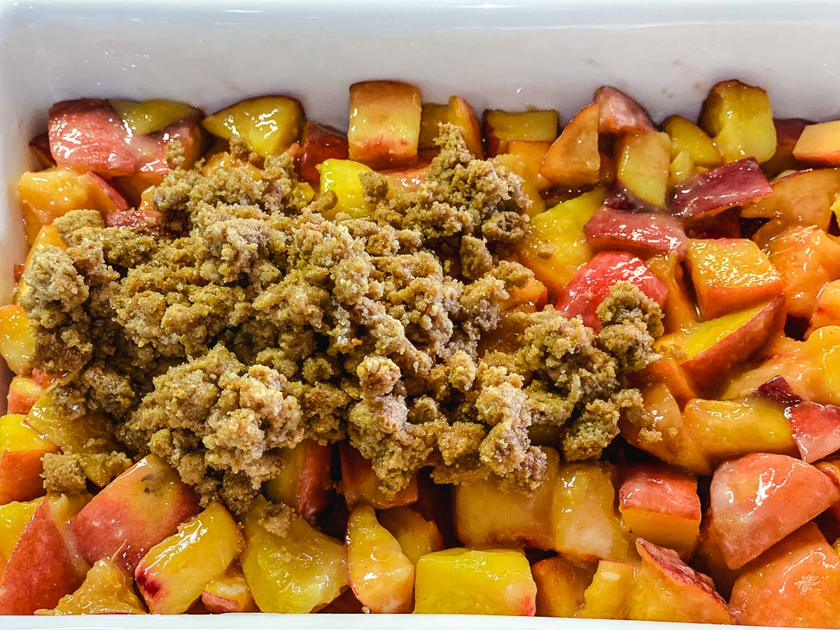 Sliced peaches in a baking sheet with cookie streusel being poured on top.