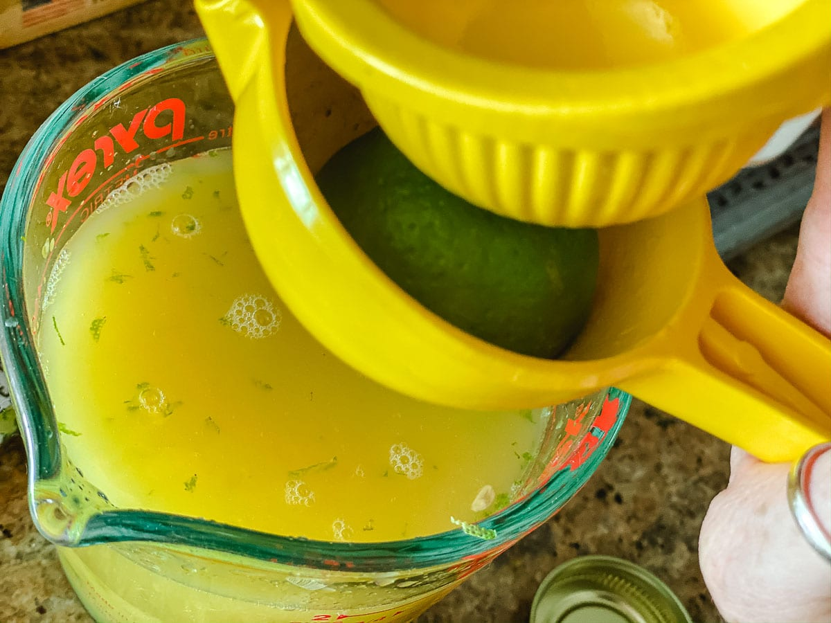 Lime being juiced into a measuring cup for the Caribbean lime steak recipe.