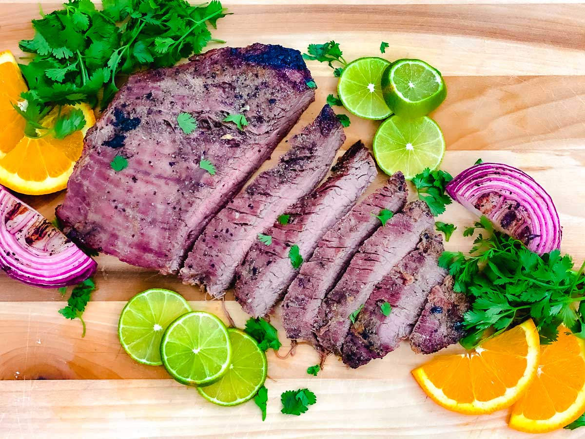 Caribbean Lime Steak on a cutting board with oranges, limes, red onions, and fresh parsley.